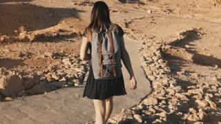 Woman with backpack explores ancient desert ruins. Beautiful European tourist walks on rocks and sand. Masada Israel 4K.