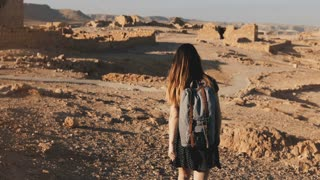 Woman with backpack explores ancient desert ruins. Beautiful European tourist walks on rocks and sand. Masada Israel 4K.