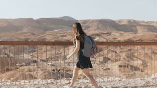 Woman with backpack looks at massive mountain view. Pretty Caucasian girl enjoys incredible desert panorama. Israel 4K.