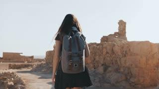 Woman with backpack walks among ancient walls. Attractive Caucasian female tourist enjoys mountain panorama. Masada. 4K.