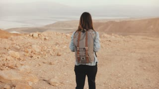Woman with backpack walks in cloudy desert. Young thoughtful Caucasian girl wanders on dry sand, smiling. Israel 4K.