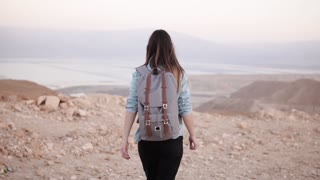 Woman with backpack walks in desert. Slow motion. Young girl wanders on dry sand and rocks. Amazing mountain scenery.