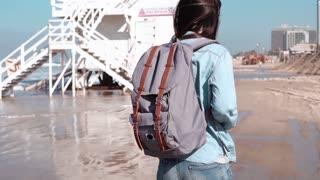Woman with backpack walks near coast guard post. Hair blowing in wind. Girl walking along ocean beach. Slow motion.