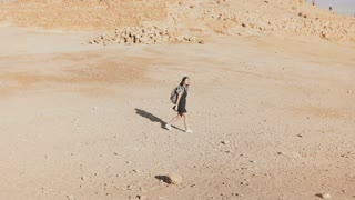 Woman with backpack walks to desert ruins. Young Caucasian female traveler on dry sand, rocks, walls. Masada Israel 4K.