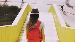 Woman with long hair walks down on a city bridge. European girl with red backpack. Yellow urban walkway walls. 4K.
