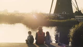 Woman with two kids sit on a lake pier on sunset. Amazing shot of a family together near water edge. 4K back view.