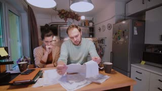 Worried couple looking at their bills in the kitchen at home. Man and woman calculating domestic accounts.