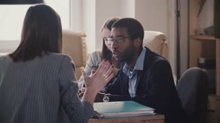 Young African American employee listens to unrecognizable female leader at modern office business meeting slow motion.