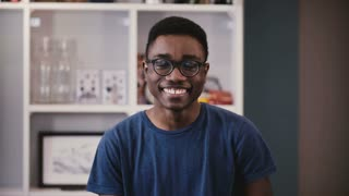 Young African American man shows different emotion. Handsome black guy in glasses laughs, then serious and again. 4K.