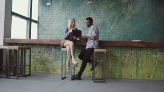 Young african businessman and caucasian businesswoman meeting at modern coworking space. Man and woman talking.