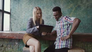 Young african man and caucasian woman sits near the bar counter at modern office and discussing the documents.