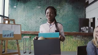 Young african businesswoman recently hired for corporate job comes into new office. Female holds box with personal belongings.