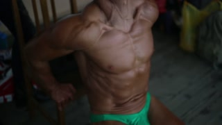 Young athletic man training forearms, biceps and triceps. He is trying hard. Bodybuilder competition background.