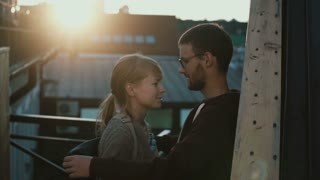Young attractive couple standing on the balcony and talking on sunset. Woman laughing and hugging the man.