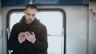 Young attractive man standing in metro and using the smartphone. Handsome male surfing the Internet in train.