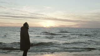 Young attractive man standing on the shore of the sea and looking on sunset. Male enjoying the landscape at beach.