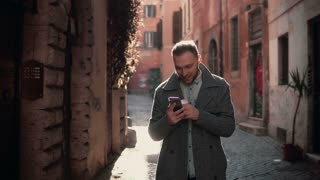 Young attractive man walking in city and using smartphone. Male chatting with friends and drinking coffee.