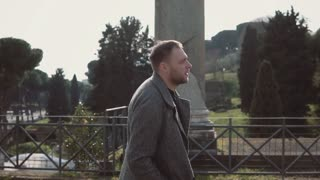 Young attractive man walks on ruin of Rome, Italy. Handsome male looking around, exploring the Roman forum. Slow motion.