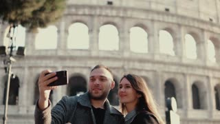 Young attractive woman and man standing near the Colosseum in Rome, Italy. Couple takes the selfie photo on smartphone.