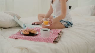 Young attractive woman drinks juice on the bed. Brunette girl surfing the Internet during breakfast, using laptop.