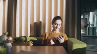 Young attractive woman sitting in the hotel and holding smartphone. Businesswoman surf the Internet on sofa in hall.