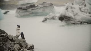 Young attractive woman sitting on the rock in ice lagoon. Tourist in lopapeysa exploring the sight of Iceland.