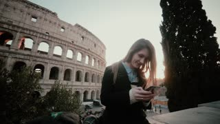 Young attractive woman standing near the Colosseum in Rome, Italy and using the smartphone. Smiling girl chatting.