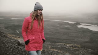 Young attractive woman walking in volcanic black mountains alone. Tourist exploring the Iceland, going to ice lagoon.