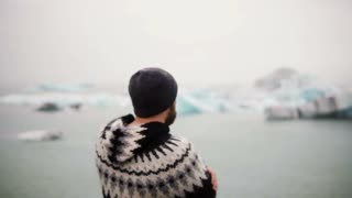 Young bearded man standing in Jokulsalon ice lagoon and looking on glaciers, North nature in Iceland.