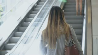 Young beautiful businesswoman going up on escalator to work in office building and using smartphone.
