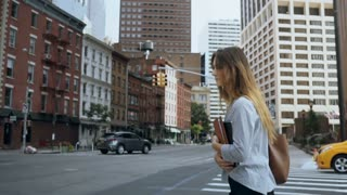 Young beautiful businesswoman holding the documents and crossing the road in financial district of New York. Slow motion