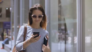 Young beautiful businesswoman in sunglasses holding documents and using smartphone, walking in the street. Slow motion.