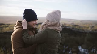 Young beautiful couple have fun together on the nature. Woman puts on the hat on man, laughings in windy day.