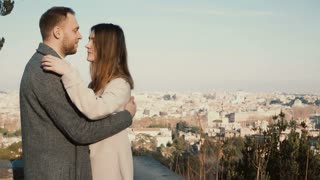 Young beautiful couple hug and kiss against the panorama of Rome, Italy. Romantic date of happy man and woman.