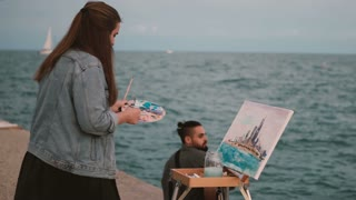 Young beautiful couple on the shore of the sea. Creative woman drawing the picture, man playing on guitar.