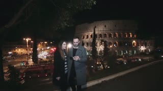 Young beautiful couple standing near the Colosseum in Rome, Italy and talking selfie photos on smartphone in the evening