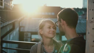 Young beautiful couple standing on the balcony and hugging on sunset. Happy man and woman on romantic date.