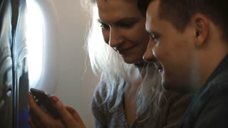 Young beautiful couple traveling by plane together. Happy man and woman using smartphone, planning to see the sights.