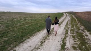 Young beautiful couple walking at the field. Aerial view, drone flying after the man and woman, they stop and kissing.