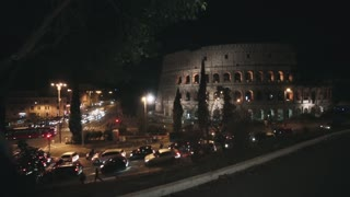 Young beautiful couple walking in the evening near the Colosseum in Rome, Italy, showing with finger to sight.