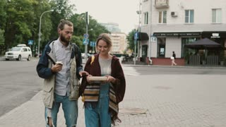 Young beautiful couple walking on the city centre together. Man eating the fast food, woman holding a box with present.