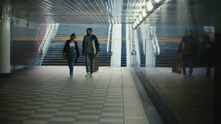 Young beautiful couple walking through the underground passage and looking on the map. Tourists in new city.