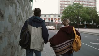 Young beautiful couple with backpack walking in the evening near the traffic road. Man and woman spending time together.