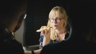 Young beautiful European girl in glasses enjoys eating pizza and talking at a casual house party with friends.