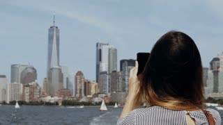 Young beautiful tourist girl taking photos of Manhattan in New York, America on smartphone from the boat on East river.