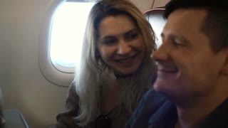 Young beautiful woman and handsome man sitting on the plane near the window and talking, laughing together.