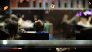 Young beautiful woman coming to cafe, sitting at the table and start to working on laptop. Female in city in the evening