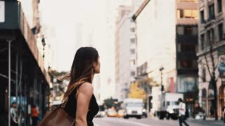 Young beautiful woman crossing the road in traffic downtown of New York, America. Female walking through the crosswalk.