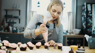 Young beautiful woman decorating the little cupcakes with cream from pastry bag. Blonde confectioner preparing an order.