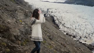 Young beautiful woman exploring the scenic places in Iceland. hiking in mountains near the Vatnajokull glaciers lagoon.